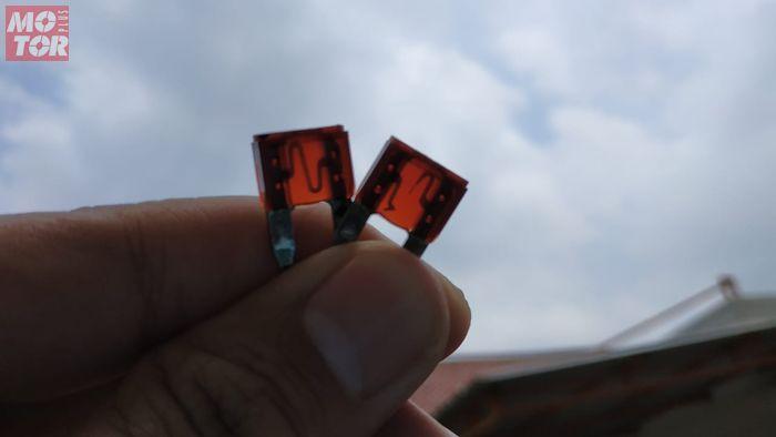 Sekring normal (kiri) dan sekring putus (kiri) dilihat dengan cara diterawang di tempat terang
