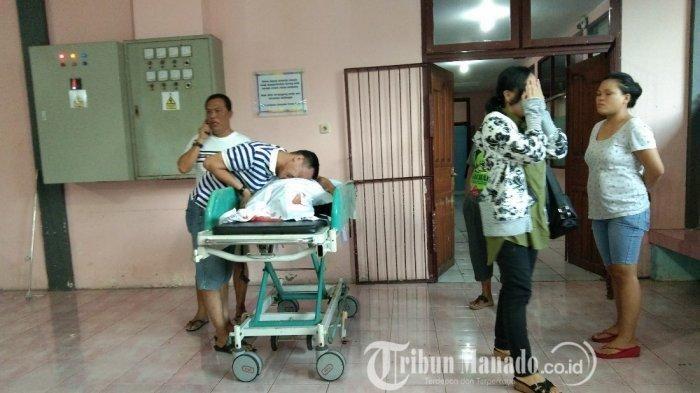 Ayah Mercelino Mogi, korban saat memeluk jenazah korban di depan ruang pemulasaran RSUP Kandou Manado.