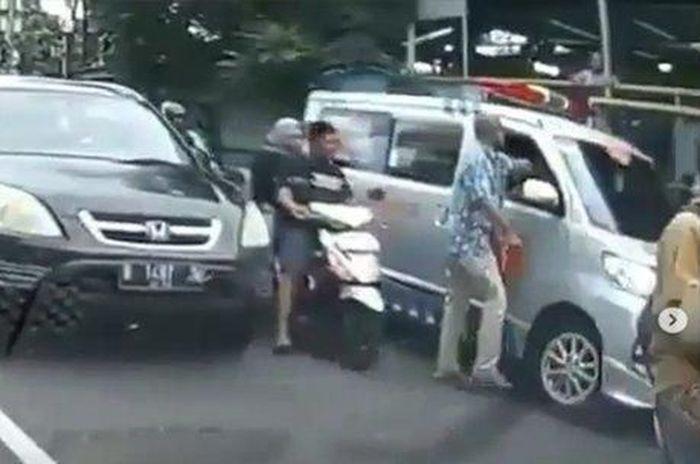 Berkepala botak pengemudi Toyota Calia sedang memukul supir ambulans.