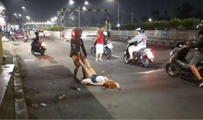 Wanita seksi berpakaian mini menarik perhatian pemotor sedang ditolong pedagang