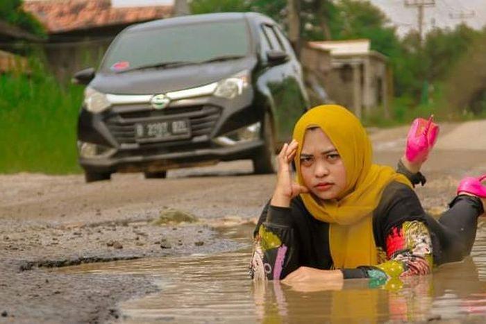Foto Ummu Hani berpose di jalan rusak