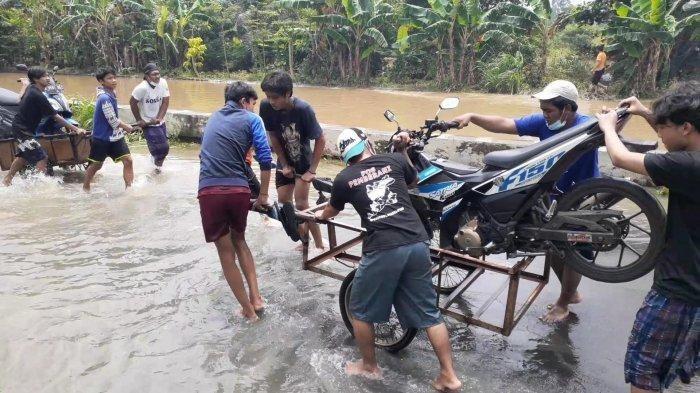 Ojek gerobak membantu bikers untuk melintas jalan banjir dengan bayar seikhlasnya