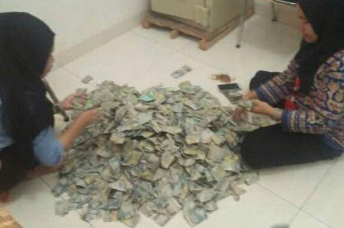 Dua orang karyawan menghitung uang Rp 2 ribuan satu karung untuk membeli motor baru.