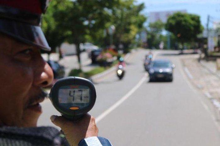 Bripka Benyamin meragakan tilang dengan speed gun di Jalan Bhayangkara, Kelurahan Gunung Elai, Kecamatan Bontang Utara, Jumat (12/1/2019).