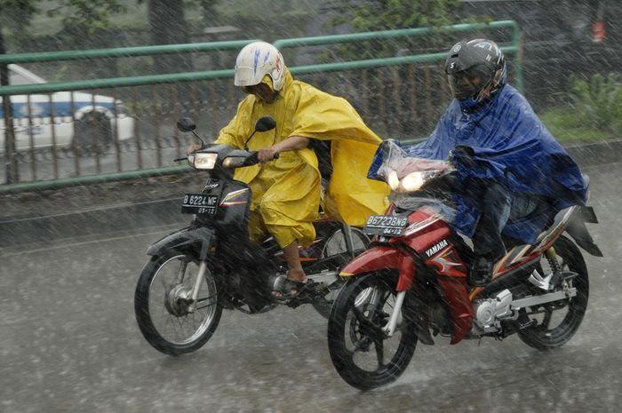 Naik motor saat hujan.