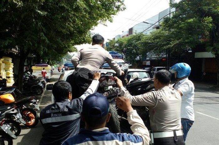 Petugas kepolisian dibantu warga saat mengangkut dua sepeda motor yang terlibat bentrok di Jalan Gat
