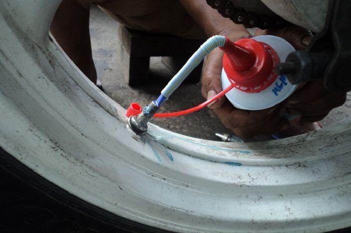 Ilustrasi ban motor pakai cairan anti bocor.