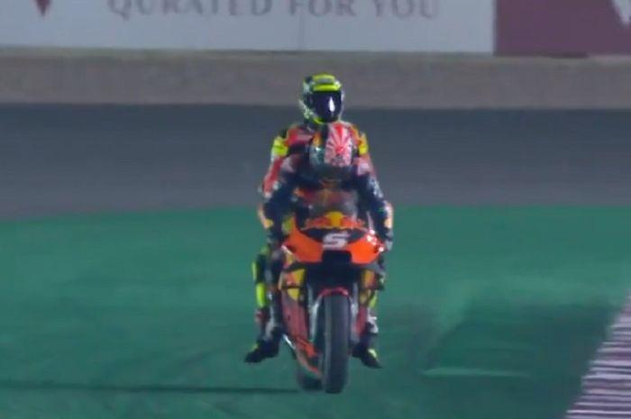 Usai terjatuh di lap terakhir MotoGP Qatar, Andrea Iannone dibonceng Johann Zarco menuju paddock.