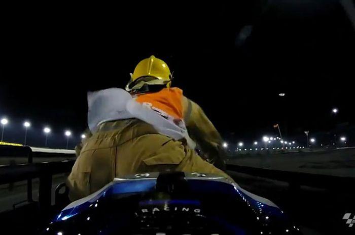 Aksi marshal menunggangi motor balap yang digendong di atas gerobak pengangkut menuju paddock