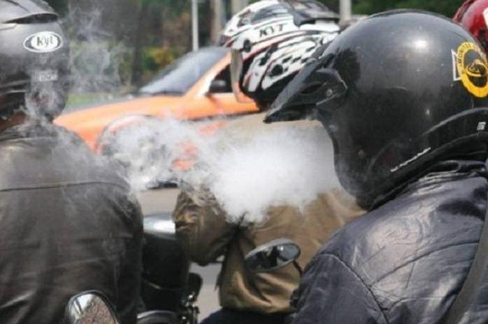 Ilustrasi naik motor sambil merokok bisa ditilang.