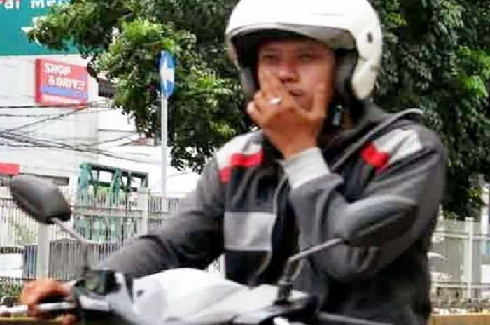 Ilustrasi pengendara motor merokok di jalan raya.