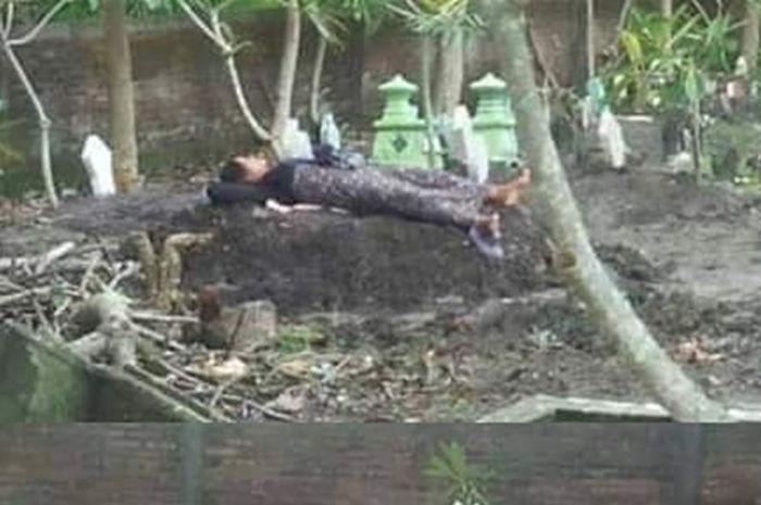 Seorang ibu tidur di atas makam anaknya