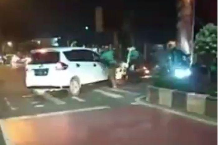 Gerombolan ojek online memukuli sebuah mobil di Bekasi