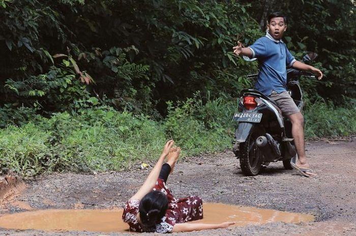 Ilustrasi naik motor di jalan rusak, pembonceng sampai terjatuh.