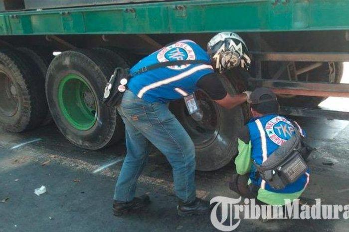 Sebuah truk kontainer diperiksa bagian bawahnya oleh relawan kecelekaan setelah melindas tiga pengendara vario di Mojokerto, Senin (1/7/2019)