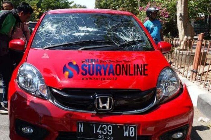 Sebuah mobil Honda Brio berwarna merah hancur setelah berhasil dikejar para pemotor dan driver ojek online.