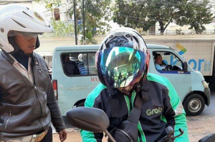 Petugas Sudinhub Jakarta Selatan memberhentikan pengendara yang berputar arah di jalur hijau yang sedang direvitalisasi di Jalan Dr Satrio, Setiabudi, Selasa (22/10/2019).