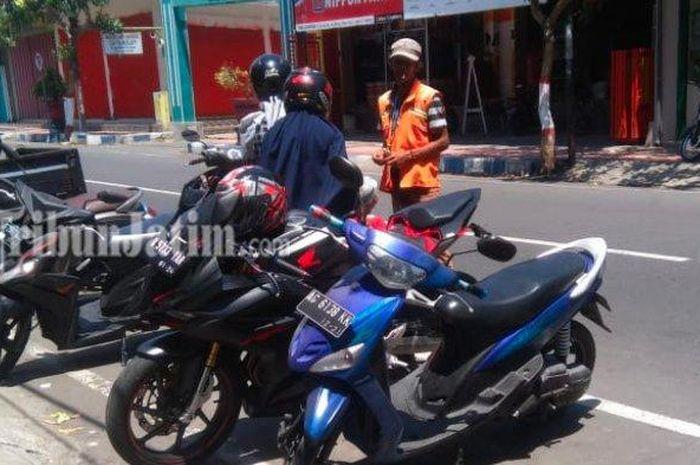 Suasana parkir di pinggir jalan kota Blitar pada Kamis (7/11/2019). Pemilik sepeda motor tetap dimintai retribusi parkir oleh jukir, meski sudah bayar parkir langganan .