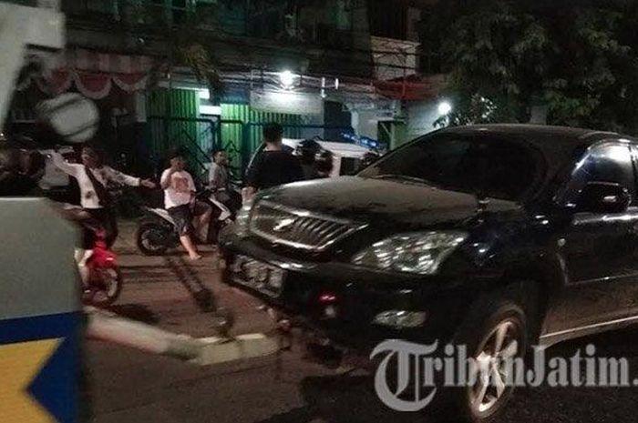 Toyota Harrier tabrak median jalan dan lindas pengendara Honda Verza di Surabaya.