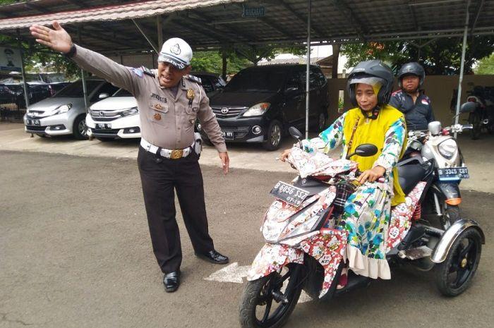 Polisi memberikan pengarahan kepada seorang pemohon SIM disabilitas.