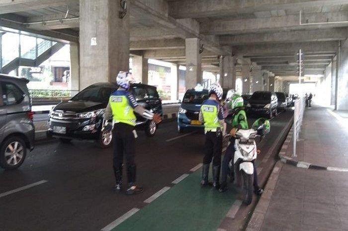 Pengendara motor yang masuk jalur sepeda ditilang polisi.