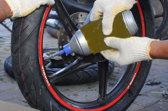 Ilustrasi penggunaan cairan anti bocor di ban motor.
