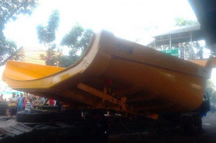 Sebuah truk trailer kecelakaan karena menghindari motor yang mendahului dari sebelah kiri