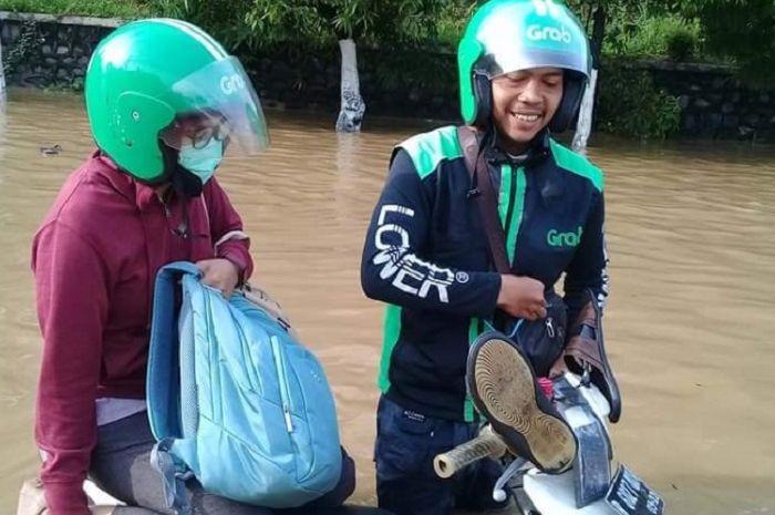 Driver ojol sabar mengantar penumpang walaupun motornya terendam banjir.