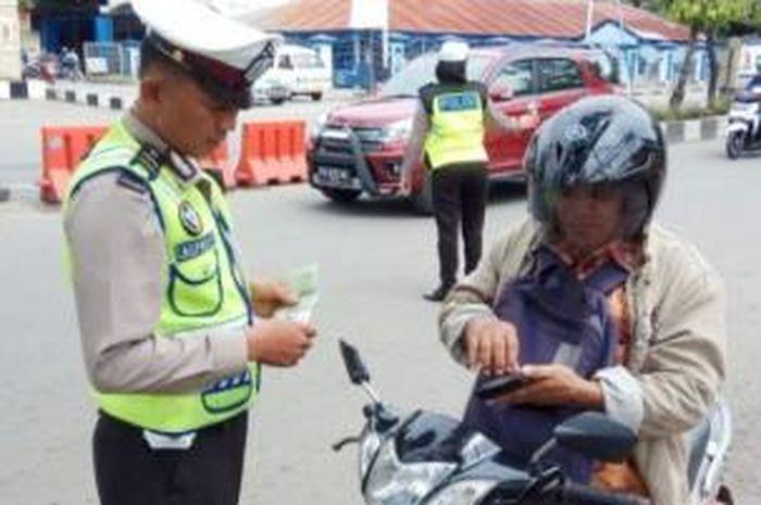 Ilustrasi polisi tilang pengendara motor.