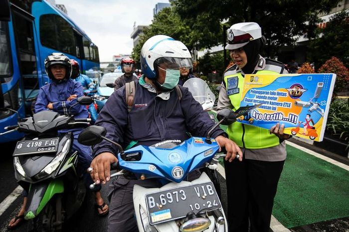 Petugas Kepolisian dari Direktorat Lalu Lintas Polda Metro Jaya menyosialisasikan sistem tilang elektronik pada kendaraan roda dua
