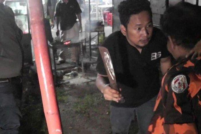 Personel Tim Rajawali Polrestro Jakarta Timur saat menunjukkan golok yang digunakan Inam Firmansyah (baju oren) untuk melukai putranya di Jatinegara, Minggu (9/2/2020).