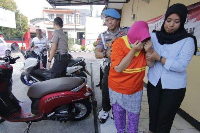 Seorang emak-emak tertunduk malu setelah ditangkap polisi.