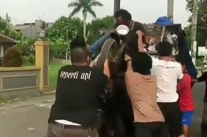 warga membantu motor pembawa sampah yang standing akibat kelebihan muatan