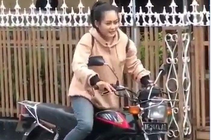Seorang perempuan terlihat berusaha menghidupkan motor klasiknya
