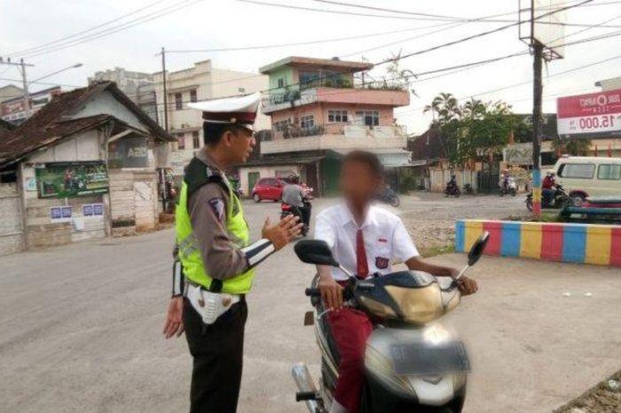 Kanit Dikyasa Lalu Lintas Polres Pringsewu Aipda Yuliansyah Idrus memberi nasihat kepada siswa SD yang mengendarai sepeda motor di Tugu Pemuda, Pringsewu, Kamis (27/2/2020).