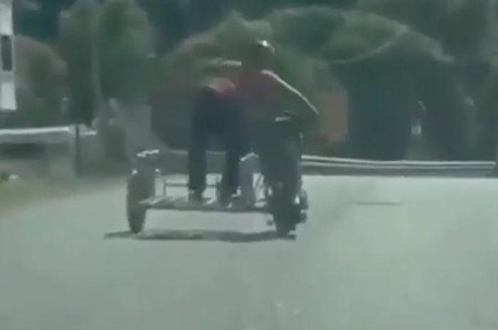 pengendara motor yang melakukan atraksi di tengah jalan raya