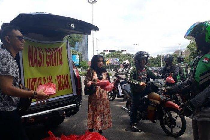 Mendadak mobil Mitsubishi Pajero yang sedang diparkir di pinggir jalan diserbu para driver ojek online (ojol) dan tukang becak di Palembang, Sumatera Selatan