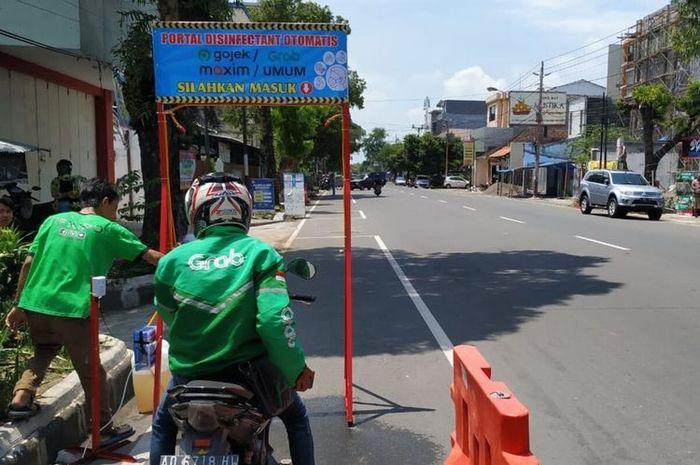 Portal disinfektan otomatis bagi driver ojol saat diuji coba di di Jalan Veteran No 62 Gajahan, Pasar Kliwon, Solo, Jawa Tengah, Minggu (29/3/2020).