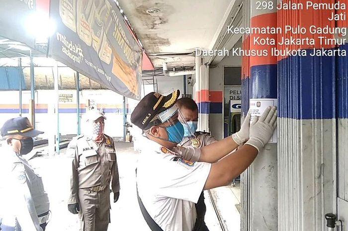 Personel gabungan yang terdiri dari TNI, Polri, Satpol PP, Dinas Perhubungan, dan pihak Kecamatan Pulogadung saat memasang stiker penutupan toko saat PSBB di wilayah Pulogadung, Jakarta Timur, Jumat (17/4/2020).