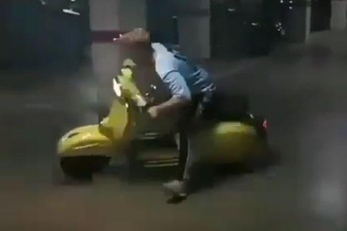 Seorang pemuda melakukan aksi drifting menggunakan motor Vespa