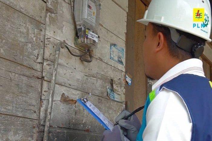 Petugas PLN saat melakukan pencatatan meter pelanggan. Banyak warga yang gagal menerima bantuan subsidi listrik.