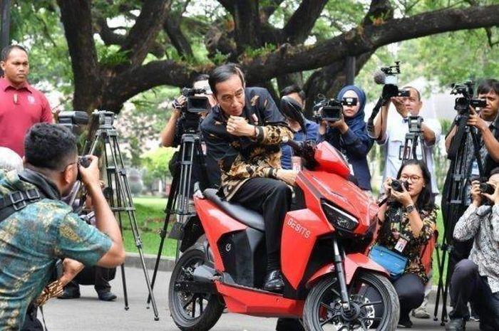 Presiden Jokowi sedang berpose diatas Motor Gesits.