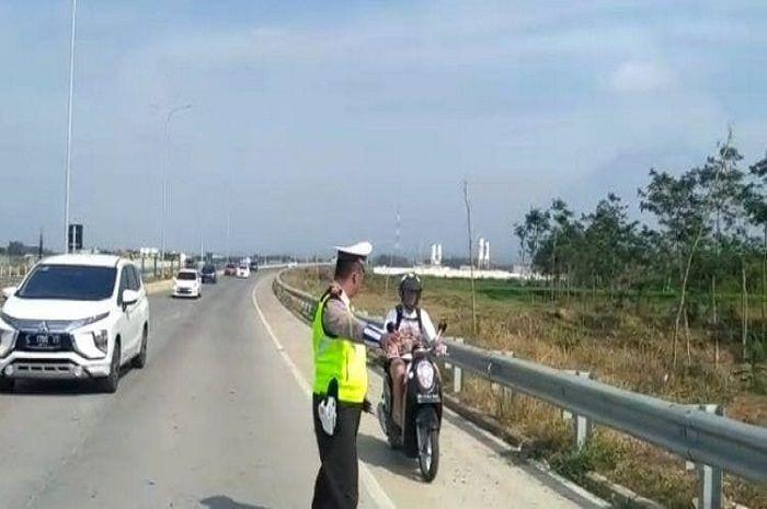 Emak-emak naik motor lewat jalan tol akhirnya dicegat polisi.