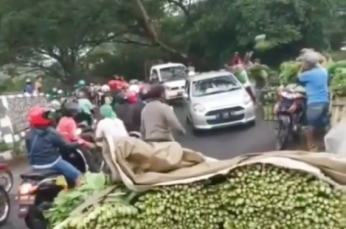 Jalanan mendadak macet, dikira terjadi tawuran pedagang sayur ternyata bagi-bagikan jualannya di tengah jalan.