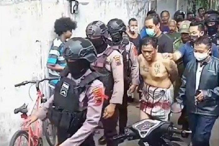 Pria penuh tato di sekujur tubuh dihajar massa sebelum dibawa polisi bersenjata lengkap. Kejadian di lingkungan RW 1, Kelurahan Kadipiro, Kecamatan Banjarsari, Kota Solo, Senin (25/5/2020).
