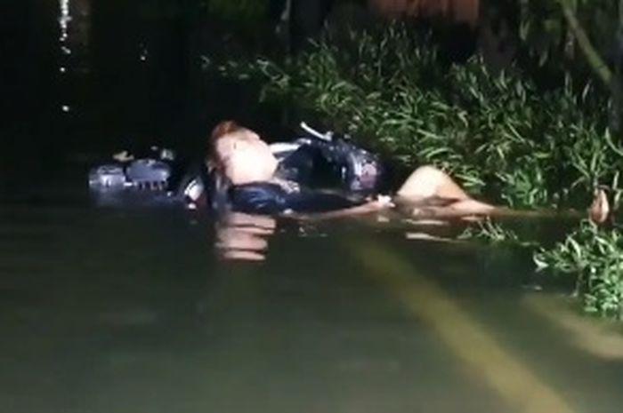Seorang pemuda ditemukan tertidur pulas saat bencana banjir rob di Jakarta Utara, Minggu (7/6/2020)