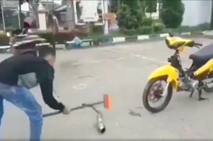 Viral video seorang pemuda menghancurkan sendiri knalpot racing miliknya menggunakan sebuah palu, Sabtu (6/6/2020).