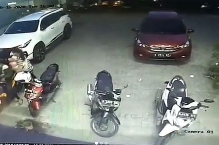Pasutri terekam kamera CCTV mengambil helm di parkiran.