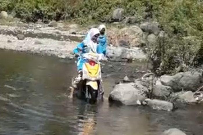Para guru trabas sungai untuk antar rapot anak muridnya