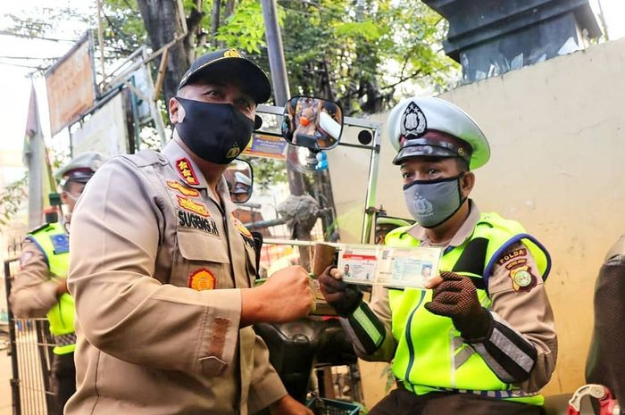 Kapolres Metro Tangerang Kota, Kombes Pol Sugeng Hariyanto memberikan SIM dan STNK ke Juru Parkir Ahmad Junaidi